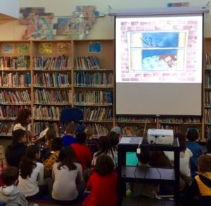 Picture of students and Veronicdoing an interactive presention at local school, complete with overhead visuals and discussion.
